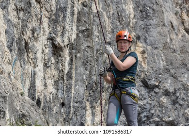 A woman climber in full gear (helmet, safety system etc) is insured by a climber standing near a rock route