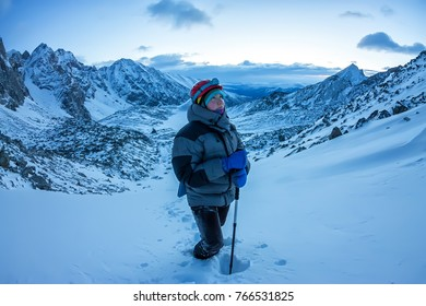 woman climber in helmet and down jacket with trekking sticks goes uphill at dawn.