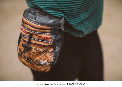 Woman climber with her climbing chalk bag. Magnesium bag.