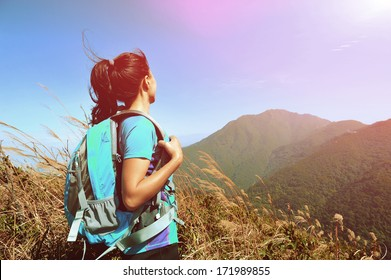 woman climber looking into the wilderness on mountain peak