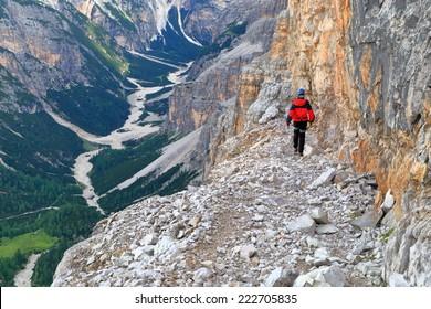 "Woman climber on exposed ledge of via ferrata ""Lipella"", Tofana massif, Dolomite Alps, Italy"