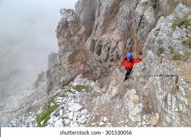 "Woman climber scrambling on rough terrain along via ferrata ""Averau"", Dolomite Alps, Italy"