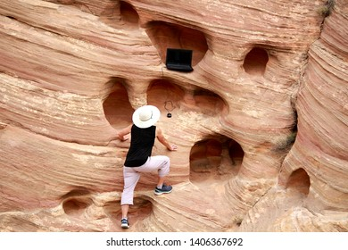 A woman climbing up a cliff to her laptop computer in the desert.