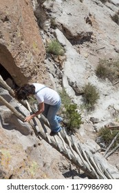 Woman climbing a ladder on a trail at the Bandelier National Monument, part of the Tsankawi Prehistoric Sites, New Mexico, USA