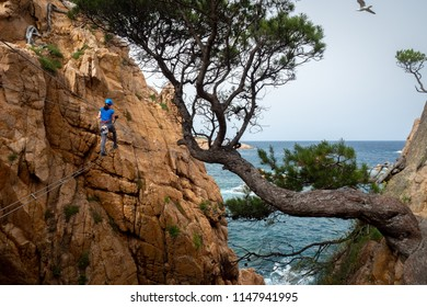 Woman climbing on Via Ferrata (Cala de Molí, Sant Feliu de Guixols, Catalonia, Spain)