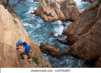 Woman climbing on Via Ferrata (Cala de Molí, Sant Feliu de Guixols, Catalonia, Spain)