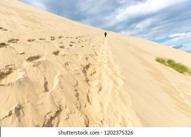 Woman climbing the Pyla dune in the Arcachon bay, Aquitaine, France