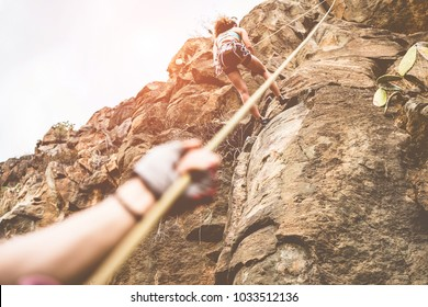 Woman climbing a rock wall in a canyon at sunset - Climbers couple training outdoor in a rocky spot - Travel, summer excursion, adrenaline and extreme sport concept - Focus on female body