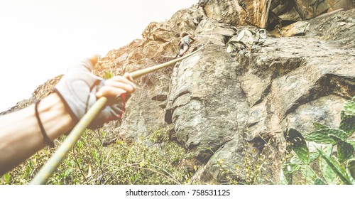 Woman climbing a rock wall in a canyon at sunset - Climbers couple training outdoor in a rocky spot - Travel, adrenaline and extreme sport concept - Focus on female body - Contrast filter