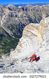 "Woman climbing the steel cable of via ferrata ""Lipella"", Tofana massif, Dolomite Alps, Italy"