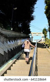 A woman climbing the stone steps of the approach of the shrine.