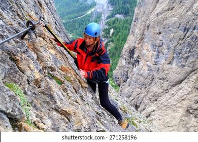 """Woman climbing under the rain on via ferrata """"Brigata Tridentina"""", Sella massif, Dolomite Alps, Italy"""