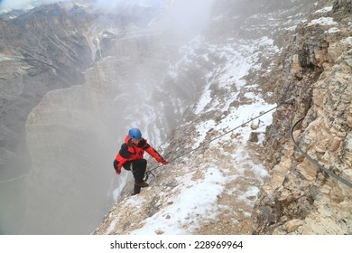 "Woman climbing via ferrata ""Lipella"" on snow covered rock, Tofana massif, Dolomite Alps, Italy"