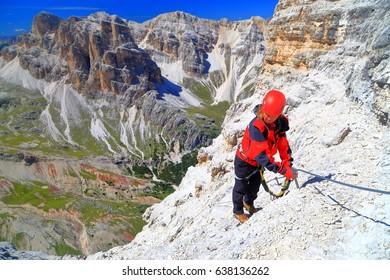 "Woman climbing via ferrata ""Lipella"", Tofana massif, Dolomite Alps, Italy"
