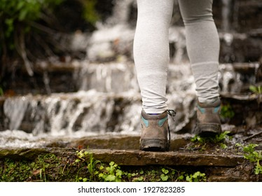 Woman climbing a waterfall, wearing gray pants and boots. Lifestyle, hike and nature concept