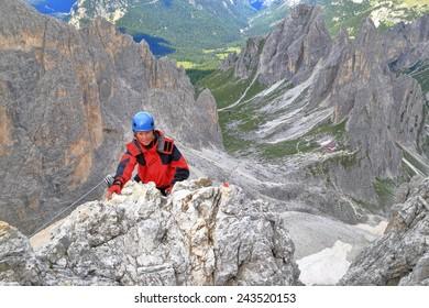 """Woman climbs aerial rock on via ferrata """"Merlone"""" in Cadini di Misurina, Dolomite Alps, Italy"""