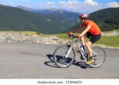 Woman climbs on a mountain road by bike