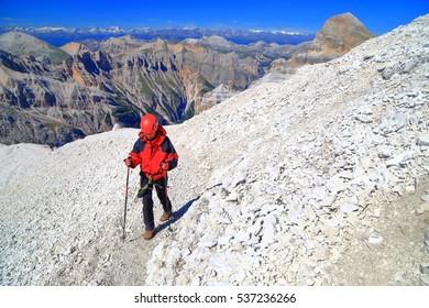 "Woman climbs rocky trail to the summit of Tofana di Rozes after completing via ferrata ""Lipella"", Tofana massif, Dolomite Alps, Italy"