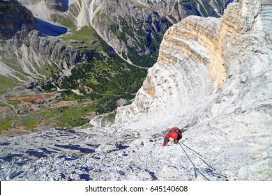 "Woman climbs rocky walls on via ferrata ""Lipella"", Tofana massif, Dolomite Alps, Italy"
