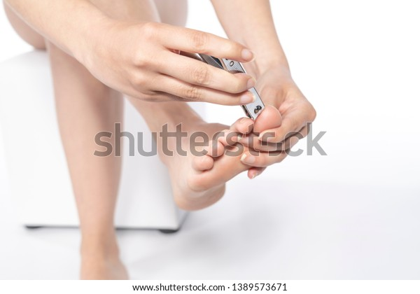Woman clipping her toenails. isolated on white background.