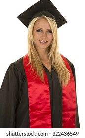 a woman up close in her graduation gown with a smile on her face.