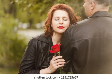 woman with closed eyes hugging a man's hand and holding a red rose n outdoors