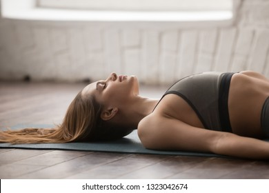 Woman with closed eyes practicing yoga, lying in Savasana, Dead Body pose on mat, beautiful girl in grey sportswear resting after working out at home or in yoga center with white walls, close up