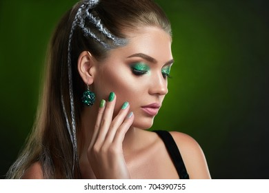 Woman with closed eyes sensuality posing, touching face and neck by hand. Beautiful brunette girl with brown eyebrows, long eyelashes, stylish green shiny makeup and manicure. Concept of cosmetics.