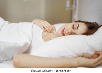 Woman with closed eyes sleeps in bed on a soft pillow