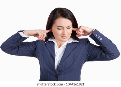Woman closes her ears with hands feeling a sharp pain. Problem with organ of hearing. Brunette isolated on white background