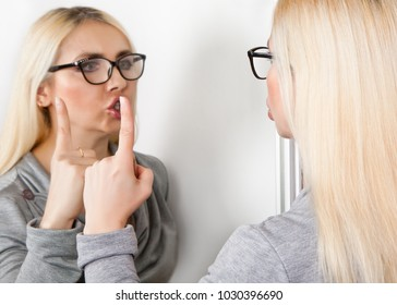 A woman closes her mouth with her index finger to her reflection in front of the mirror. A sign of silence.