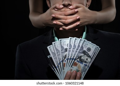 Woman closes mouth a man in suit holds money. Bribe and Corruption. Free speach