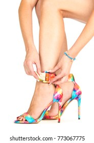 woman is closing ankle strap of high heels shoes in multiple colors.