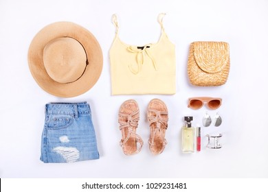 Woman clothes & accessories: yellow top, jeans skirt, perfume, rope sandals, sunglasses, straw hat, white background. Flat lay trendy feminine fashion. Boho chic style bracelet. Top view, copy space.