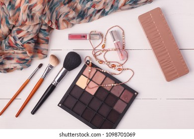Woman clothing, cosmetics and accessories placed on a wooden background.