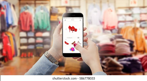 Woman in clothing store holding phone in hands and searching online shoes