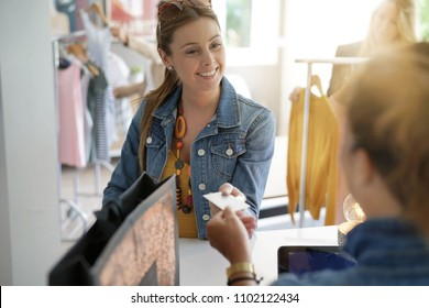 Woman in clothing store paying with credit card