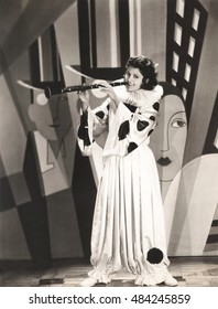 Woman in clown costume playing clarinet