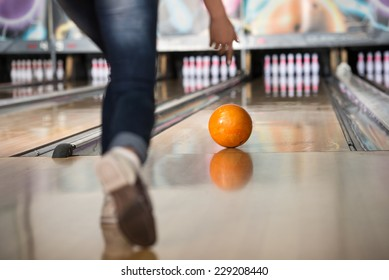 Woman in club for bowling is throwing ball.