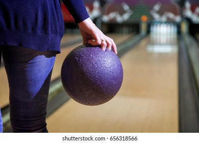 Woman in club for bowling is throwing ball