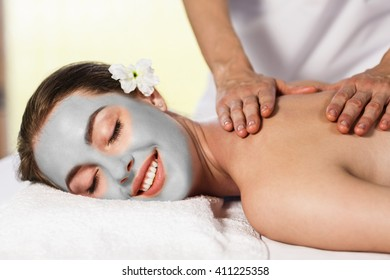 Woman with cly mask enjoying massage.