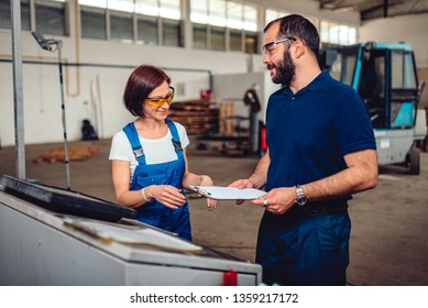 Woman CNC Machine Operator consulting with Engineer in the industrial hall