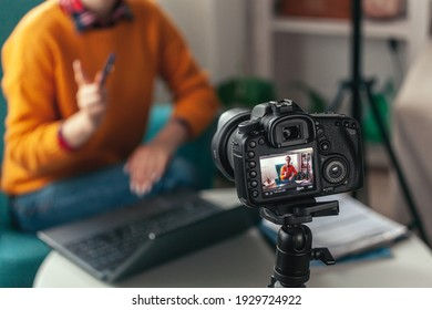 Woman coach or psychologist conducts online conference and records video on the camera for blog at home
