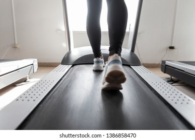 Woman coach trains on a treadmill in a gym. Girl runs on a treadmill. Sports exercises for weight loss. Rear view of female legs in sneakers. Close-up.