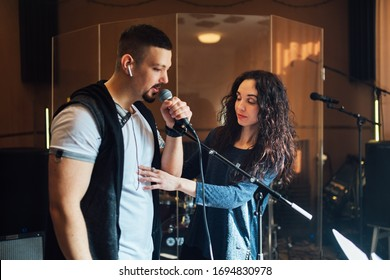 Woman coaching a male vocalist or singer