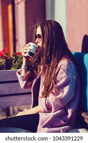 Woman in coat drinking coffee and laughing. Summer.