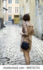Woman at coat with handbag turned back