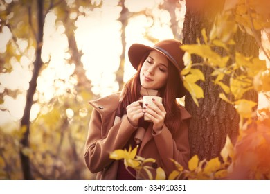Woman in coat with hat and scarf holding cup in autumn park