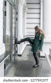 woman in a coat kicks her foot in the closed door