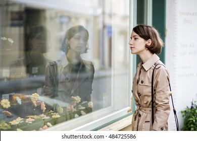 Woman at coat looking at store showcase